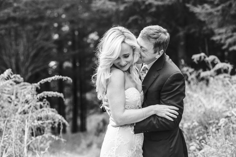 Bride and groom getting married in Scotland outside in woods with groom kissing brides cheek