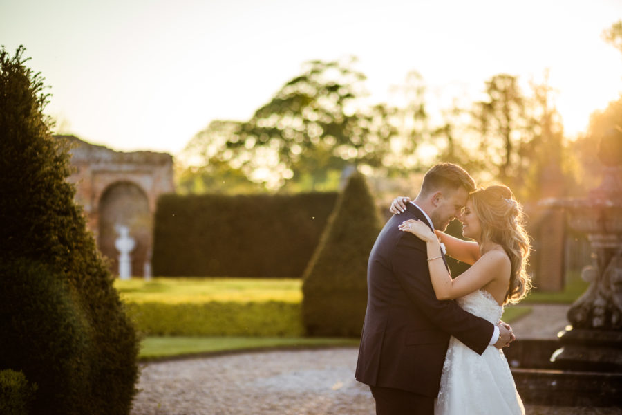 Sunset wedding photography_oxnead hall_norfolk_couple hugging in romantic embrace next to fountain in gardens